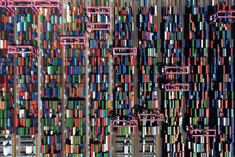 Shipping containers sit stacked among gantry cranes in this aerial photograph taken above the BNCT Co. container terminal at
