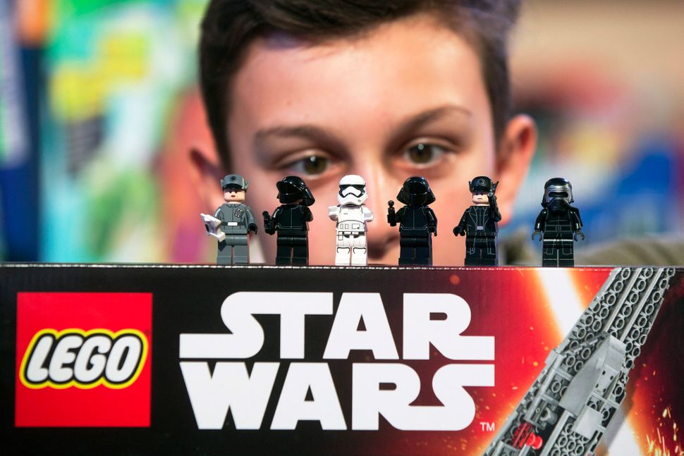 "A child looks at Lego figurines from the Star Wars ""Kylo Ren's Command Shuttle,"" manufactured by Lego A/S, as it sits on disp"