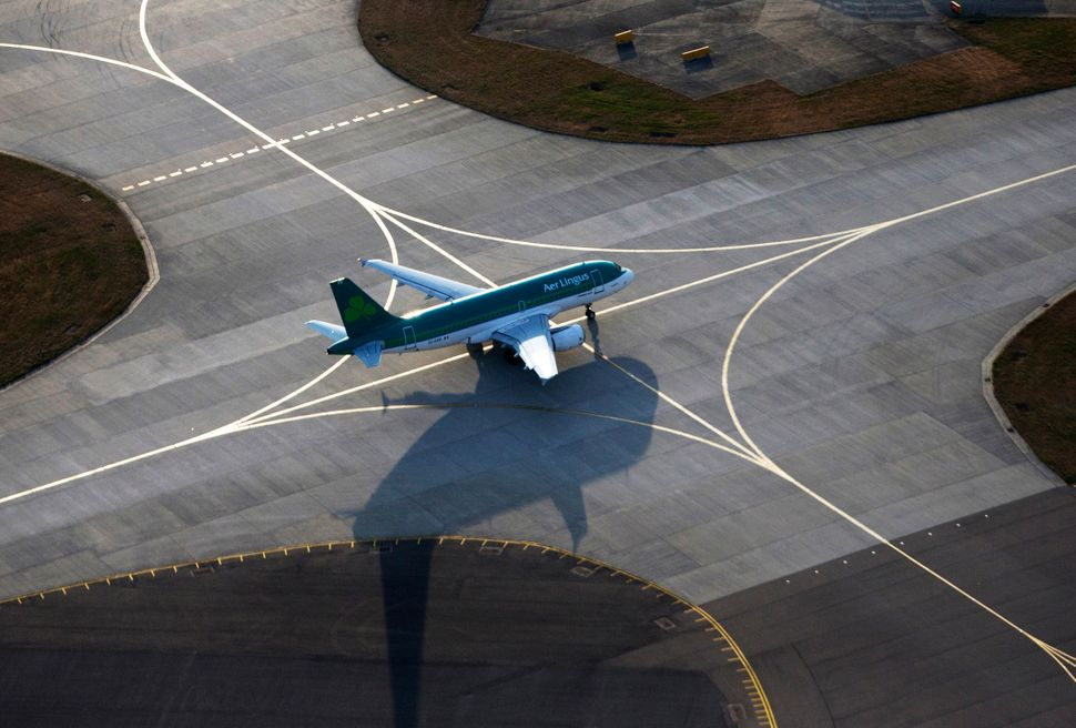 An Aer Lingus aircraft, operated by Aer Lingus Group Plc, stands on the perimeter of the runway at London Heathrow Airport, i