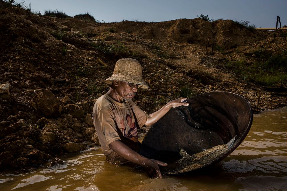 Traditional miner Sya'rani (54), who has been mining for 30 years, washes mud in conical bowls known as Linggang as they sear