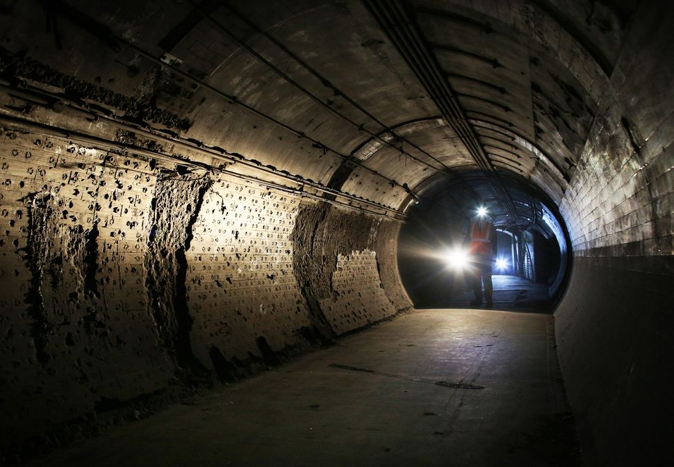 A worker passes through part of the disused Down Street underground station on May 18, 2015, in London, England. The disused