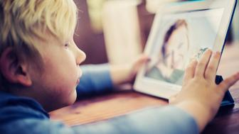 Little boy talking to his Mother on an electronic tablet over the internet