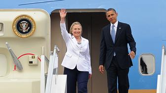 US President Barack Obama (R) and US Secretary of State Hillary Clinton wave on arrival at the Yangon International Airport on November 19, 2012. Obama arrived in Myanmar for a historic visit aimed at encouraging a string of dramatic political reforms in the former pariah state.         AFP PHOTO / Soe Than WIN        (Photo credit should read Soe Than WIN/AFP/Getty Images)