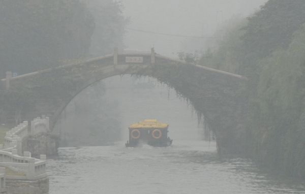 A tour boat sails down a river in Suzhou on Monday.