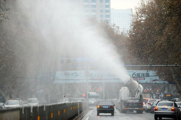A vehicle squirts water into the air to dispel smog.