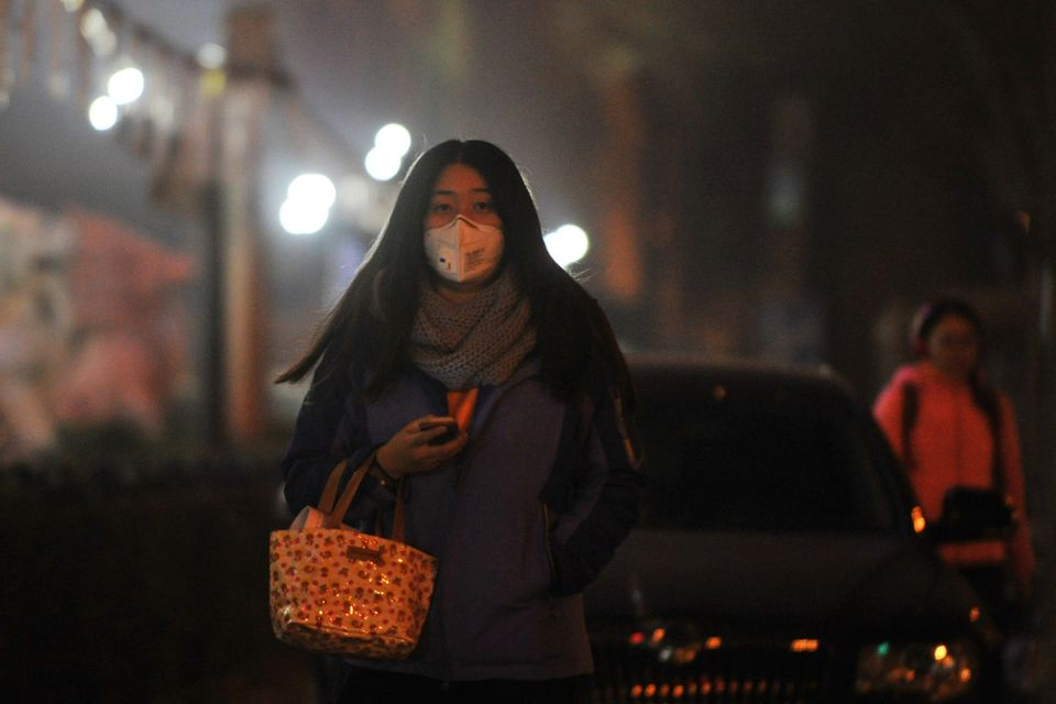A woman wears a breathing mask while walking through smog in Beijing. A red alert in the city is scheduled to&