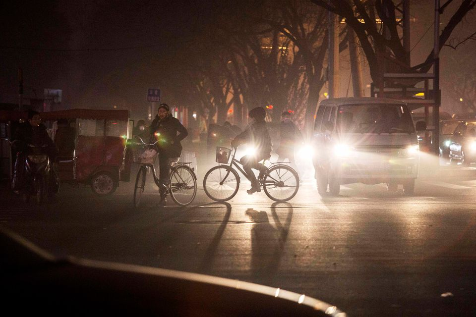 Commuters ride bicycles in smog during a day of high pollution on December 1, 2015 in Beijing, China. China's capital and man