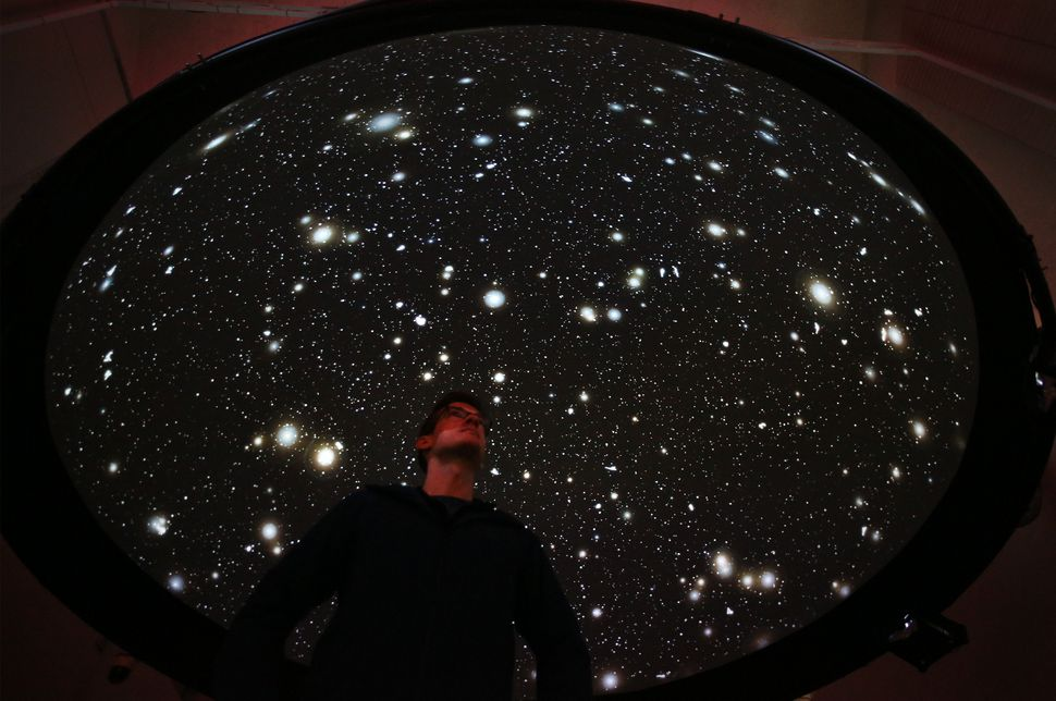 "A member of staff looks up at the ""Black Shoals: Dark Matter"" projection at the Big Bang Data exhibition at Somerset House on"