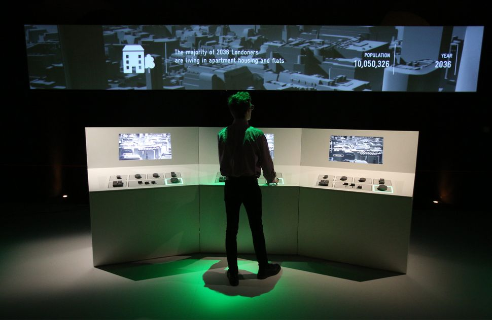 A staff member plays with a game that builds a future London at the Big Bang Data exhibition at Somerset House on Dec. 2, 201