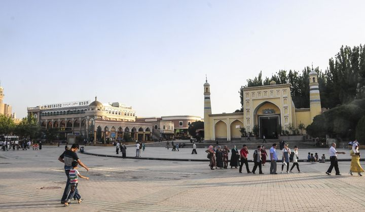 Uighur people walk outside the Id Kah Mosque in northwestern China's Xinjiang autonomous region on July 7, 2015.