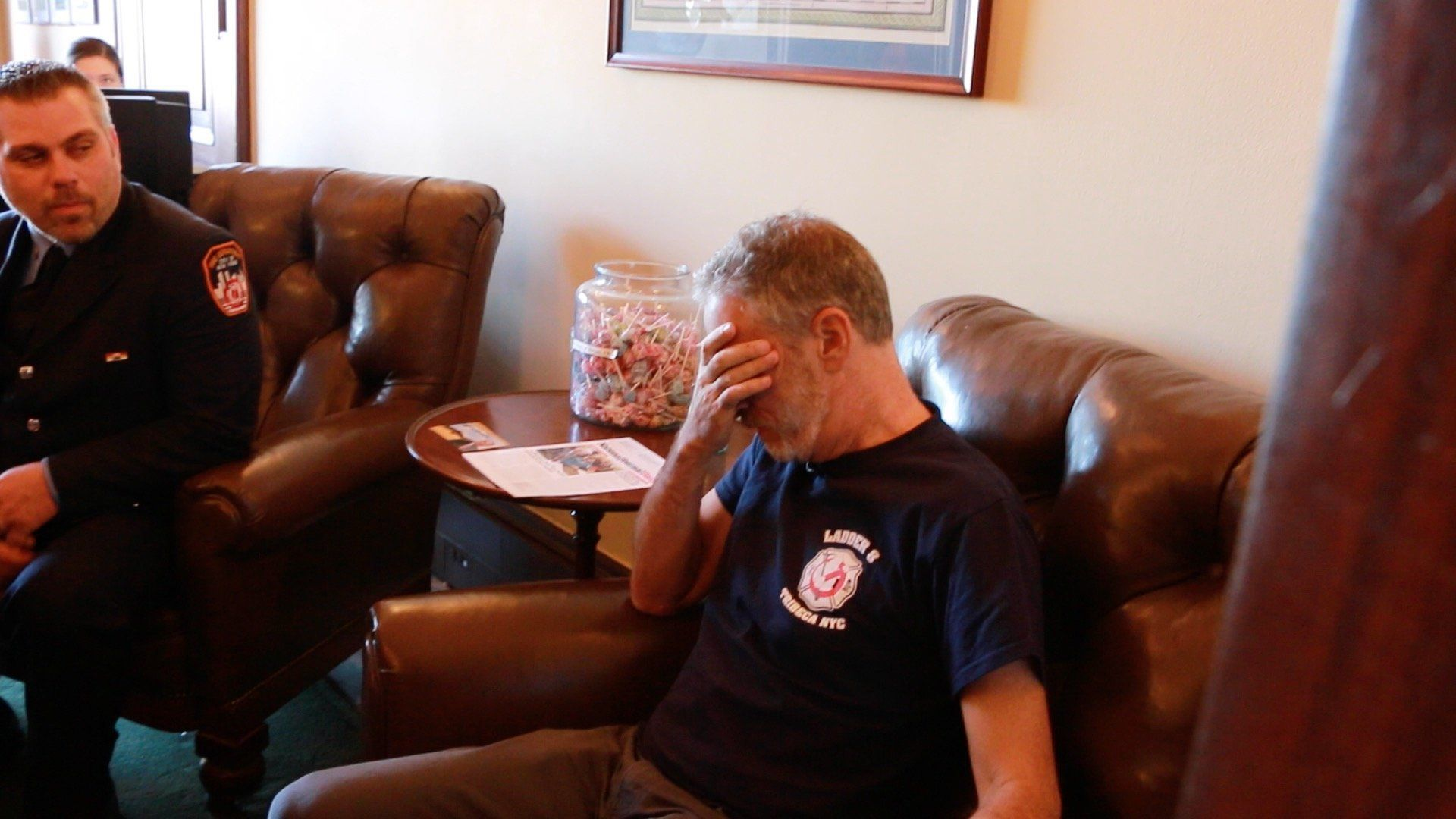 Jon Stewart bows his head and covers his eyes in a U.S. Senate office.