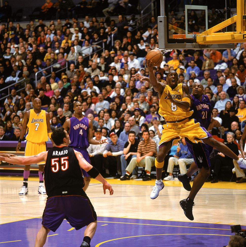 Bryant performs some acrobaticsin the lane against Lamond Murray and the Toronto Raptors on Dec.28, 2004.