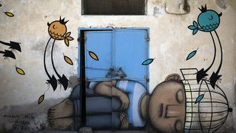TO GO WITH AFP STORY BY ANTOINE LAMBROSCHINI - FILES - A mural by French artist SETH decorates a wall in the village of Erriadh, on the Tunisian island of Djerba, on August 7, 2014, as part of the artistic project 'Djerbahood'. Nearly 100 artists from 30 different nationalities were invited by French-Tunisian organizer Mehdi Ben Cheikh to take part in an initiative to turn Djerba's Erriadh town into an 'open sky museum'. The village of Erriadh is one of the oldest in Tunisia where Jews, Muslims and Christians have lived together for centuries. AFP PHOTO / JOEL SAGET  = RESTRICTED TO EDITORIAL USE, MANDATORY MENTION OF THE ARTIST UPON PUBLICATION, TO ILLUSTRATE THE EVENT AS SPECIFIED IN THE CAPTION =        (Photo credit should read JOEL SAGET/AFP/Getty Images)