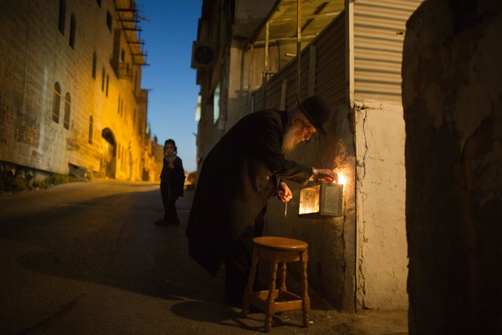 An ultra-orthodox Jewish man lights candles on the sixth night of the Jewish holiday of Hanukkah, in a religious neighborhood