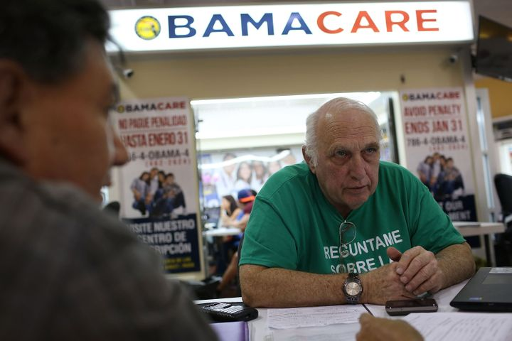 Insurance agent Antonio Galis, left, discusses health insurance plans with a client at the Mall of the Americas in Miami on Nov. 2.