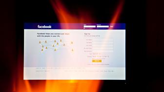 The Facebook website is seen through fire on a computer screen in this photo arranged in Beijing, China, on Thursday, Feb. 17, 2011. Facebook Inc. users in China, blocked by firewalls in the country since 2009, have more than doubled in the past month to exceed 700,000 using a growing number of so-called Virtual Private Network (VPN) services to circumvent censors in the world's biggest Internet market. Photographer: Nelson Ching/Bloomberg via Getty Images