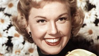 UNSPECIFIED - CIRCA 1950: (AUSTRALIA OUT) Photo of American singer and actress Doris Day posed wearing a yellow neckerchief in front of a backdrop of large daisies circa 1950. (Photo by GAB Archive/Redferns)