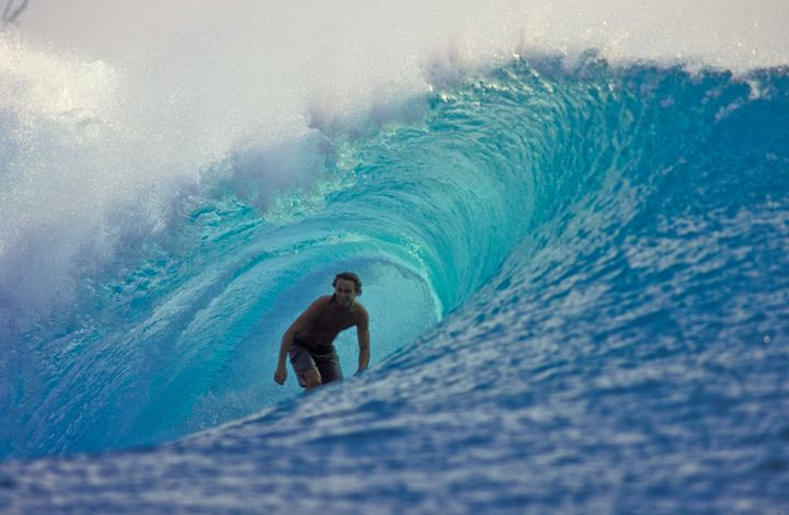 A surfer catches a wave in the Mentawai Islands.