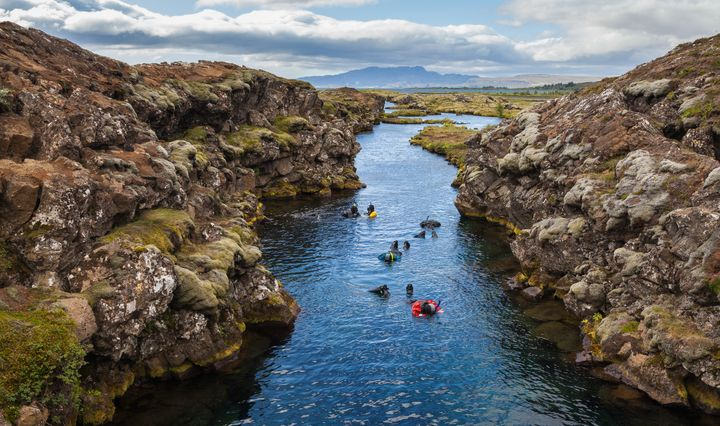 "Snorkelers explore the ""<a href=""https://www.dive.is/dive-sites/silfra/"">clearest water on Earth</a>"" at&nbsp;Silfra Canyon, the crack between the North American and Eurasian continents."