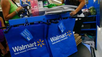 A cashier scans school supplies for a customer at a Wal-Mart Stores Inc. location in the Porter Ranch neighborhood of Los Angeles, California, U.S., on Thursday, August 6, 2015. More U.S. parents are planning to increase back-to-school spending this fall than at any time in at least the past four years, according to a survey released Tuesday by the International Council of Shopping enters. Photographer: Patrick Fallon/Bloomberg via Getty Images