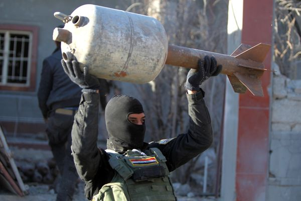 A member of the Iraqi counter-terrorism forces carries a rocket, in Ramadi, Iraq, on Dec. 9, 2015.