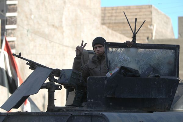 A member of Iraq's counter-terrorism forces flashes the V sign for victory in the al-Tameem district of Ramadi, Iraq, on Dec.