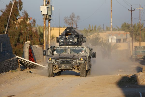 Iraqi troops and allied paramilitaries drive down a street in Husayba, a town five miles east of Ramadi, Iraq, on Dec. 6, 201