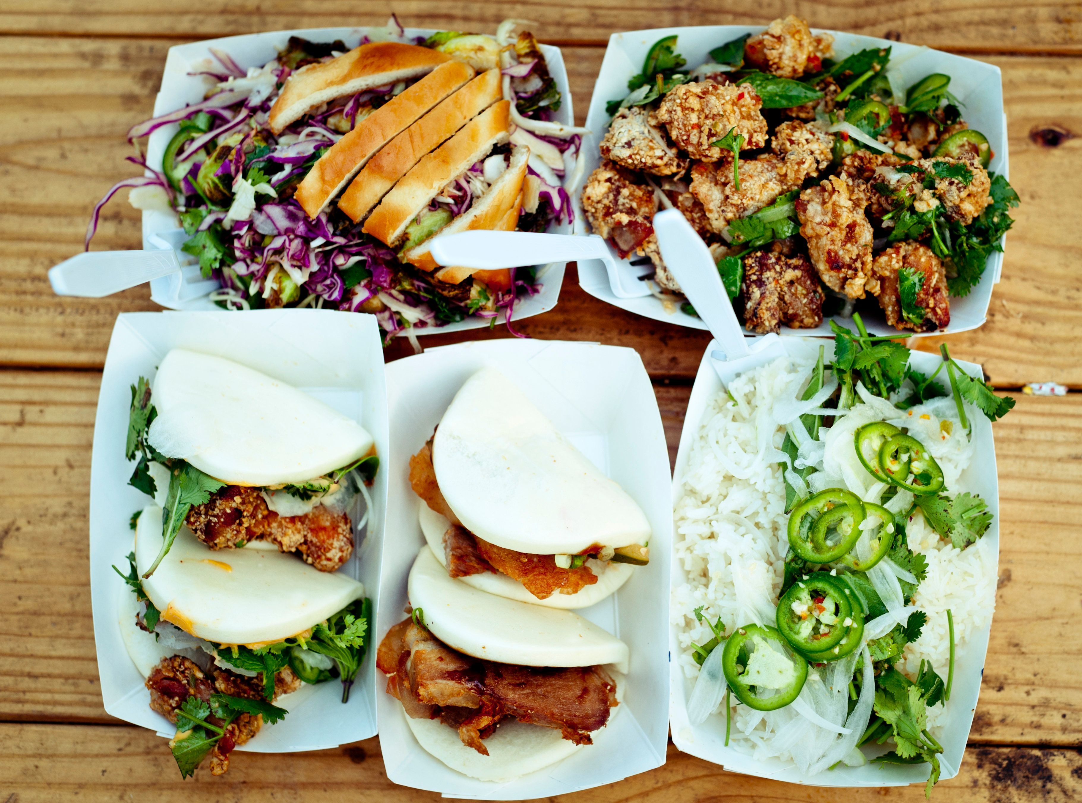 6 Dishes from Texas Korean fusion food truck placed on top of outdoor wooden table.