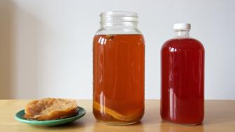 Three parts of the process of making kombucha (a fermented tea drink) at home. At centre, a large jar where strong tea has been blended with sugar, filtered water and some previously made kombucha as a starter, with a mother floating inside to help the ferment. At left, a kombucha 'mother', or SCOBY - symbiotic culture of bacteria and yeast. At right, some completed kombucha has been bottled with raspberries added for flavour and colour. Kombucha is a trendy drink that is said to be nutritious and have probiotic properties.