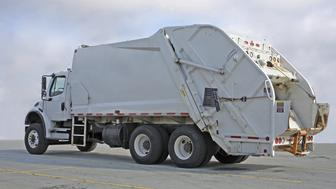 Rear quarter view of a waste management vehicle, aka garbage truck.