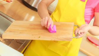 People, housework and housekeeping concept. Woman doing the tidying up in kitchen cleaning wooden cutting board with rag sponge