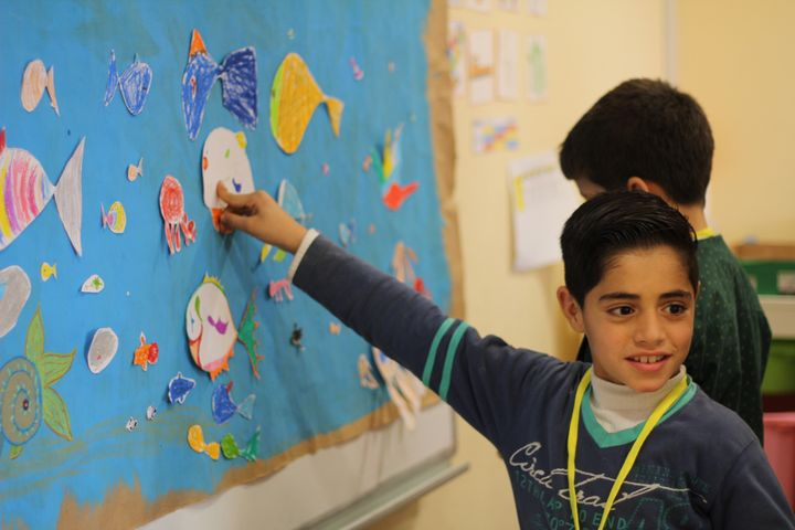 A Syrian boy points to a drawing of a fish during a psychosocial counseling workshop put on by Project Lift.