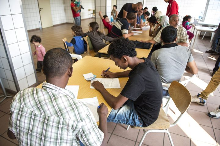 Refugees arriving in Germany fill out screening forms on August 13, 2015.