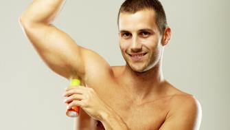 Studio shot of an muscular  man holding deodorant and smiling. Grey background