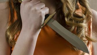 Close up of a young woman holding a knife