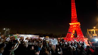 NGO representatives gather next to on the mini red Eiffel Tower after a sit-in protest closed to the plenary session to denounce the first draft COP21 Climate Conference agreement, and put pressure to reach an international agreement to limit global warming, during the COP21, United Nations Climate Change Conference in Le Bourget, north of Paris, France, Wednesday, Dec. 9, 2015. (AP Photo/Francois Mori)