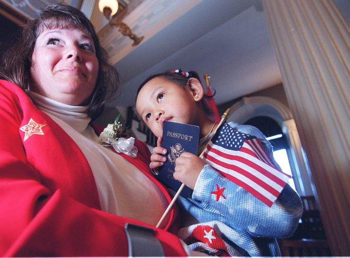 Madison Noelle Hao Collins, 3, celebrates with her mother, Judy Collins, and her new U.S. passport at Boston'sFaneuil H