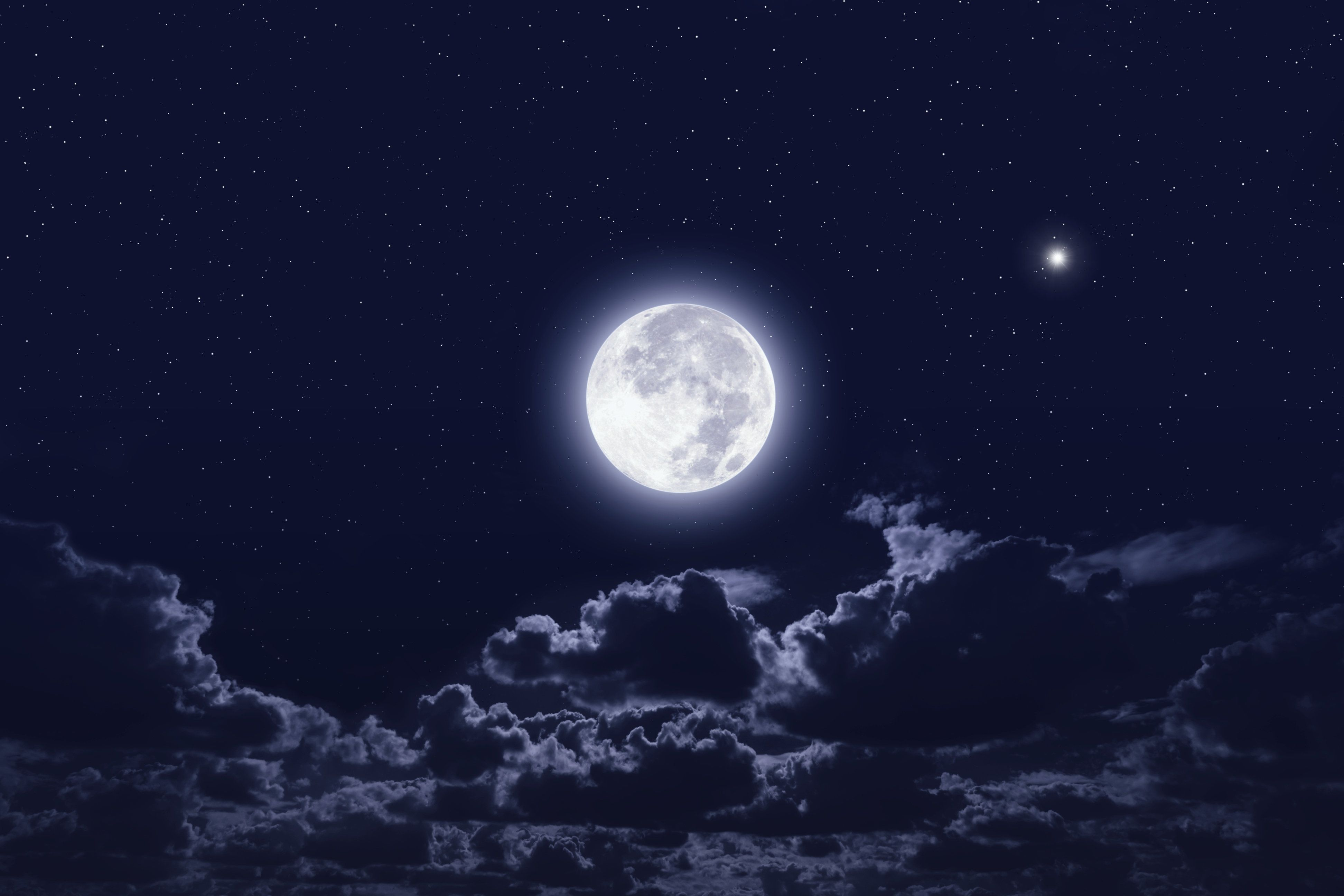 Full moon in dark night sky with stars and clouds. Elements of this image furnished by NASA