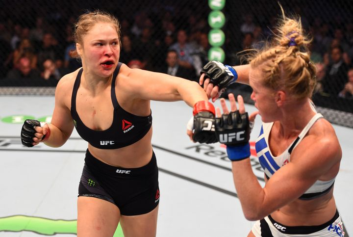 Ronda Rousey (L) punches Holly Holm (R) in their UFC women's bantamweight championship bout in Melbourne, Australia, on Nov.