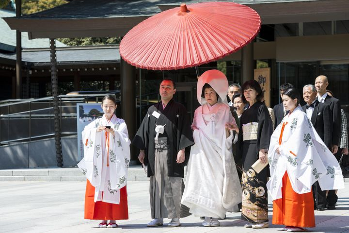 Japanese bride and groom with family and shrine maidens (Miko) at Shinto wedding ceremony, Meiji Jingu shrine, Tokyo, Japan