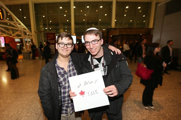 "Chaim Ifrah and Shai Reef, Jewish Torontonians, wait at terminal one for refugees with a 'Welcome to Canada"" sign."