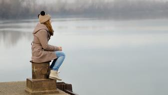 Lonely teenage girl sitting on the dock on cold winter day.