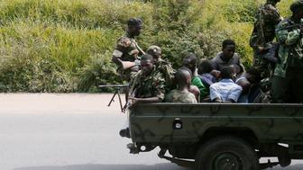 TOPSHOT - A military vehicle, carrying men tied up, drives through the Musaga neighbourhood of the city of Bujumbura on December 11, 2015. Heavily-armed gunmen launched coordinated assaults on three army barracks in the Burundian capital on December 11 leaving at least a dozen dead in the worst unrest since a failed May coup. / AFP / STRINGER        (Photo credit should read STRINGER/AFP/Getty Images)