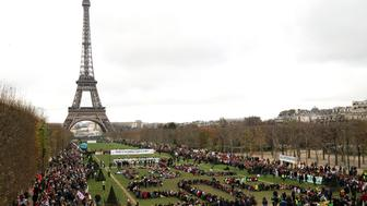TOPSHOT - Several Non Governmental Organisations (NGO) gather to form a human chain  reading '+3°C SOS' on the Champs de Mars near the Eiffel Tower on December 12, 2015 in Paris on the sidelines of the COP21, the UN conference on global warming. French hosts submit the final version of a global climate-saving pact to negotiators at UN Conference on december 12. The goal is for ministers to approve the agreement by the end of the day but that could be extended one more day. / AFP / ALAIN JOCARD        (Photo credit should read ALAIN JOCARD/AFP/Getty Images)