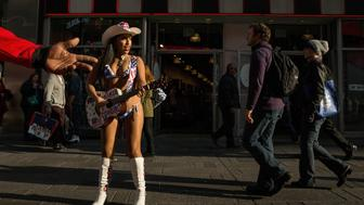 NEW YORK, NY - DECEMBER 10:  Patricia Burck, who performs in Times Square as the Naked Cowgirl, dresses in a bikini thanks to 60 degree weather on December 10, 2015 in New York City. Temperatures have been unusually warm despite the winter season.  (Photo by Andrew Burton/Getty Images)