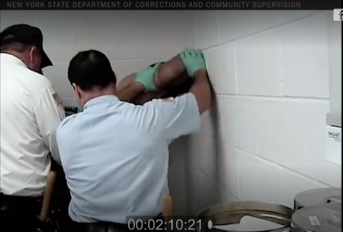 Corrections officers pin Strickland to the wall.