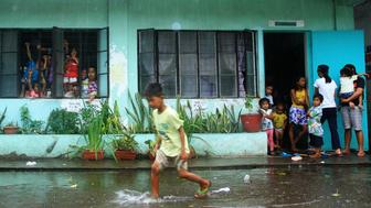 A young evacuee wades through flooded school grounds while others look on from a school building being used as an evacuation center in the city of Legaspi in Albay province, south of Manila on December 14, 2015, as typhoon Melor approaches the city. More than 700,000 people fled the central Philippines amid threats of giant waves, floods and landslides as powerful Typhoon Melor approached the archipelago nation, officials said December 14.  AFP PHOTO/Charism Sayat / AFP / Charism SAYAT        (Photo credit should read CHARISM SAYAT/AFP/Getty Images)
