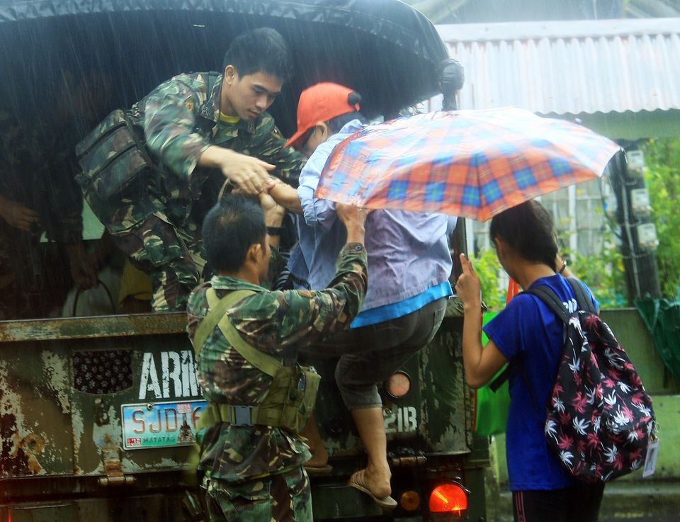 Military personnel evacuate residents from a village in the central Philippine city of Legazpi.
