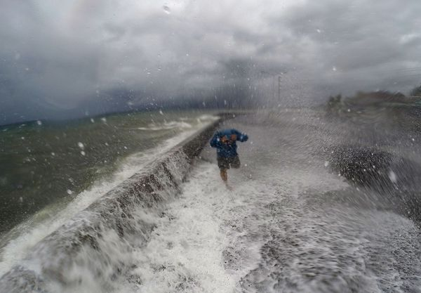 A resident walks past waves spilling over a wall onto a coastal road in Legazpi.