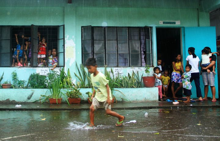 A young evacuee wades through flooded school grounds while others look on from a school building being used as an evacuation